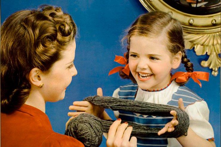 little girl and mom winding ball of yarn