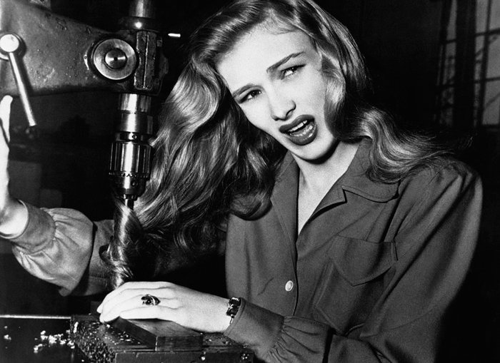 US actress Veronica Lake illustrates what can happen to women war workers who wear their hair long while working at their benches, 1943.